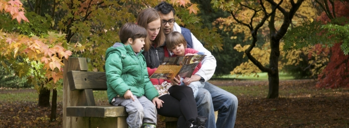 Family of four sat on a bench together exploring a visitor leaflet